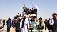 In this photo taken on June 17, 2018, Afghan Taliban militants and residents stand on a armoured Humvee vehicle of the Afghan National Army (ANA) as they celebrate ceasefire on the third day of Eid in Maiwand district of Kandahar province. - Extraordinary scenes of Afghan Taliban and security forces spontaneously celebrating a historic ceasefire showed many fighters on both sides were fed up with the conflict, raising hopes that peace in the war-torn country was possible, analysts said. (Photo credit should read JAVED TANVEER/AFP via Getty Images)