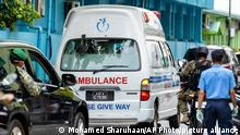 Maldivian government security officers escort an ambulance carrying former president and current Parliament Speaker Mohamed Nasheed