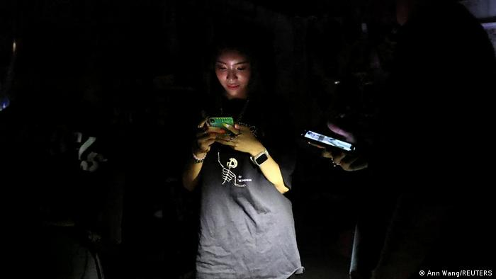 A smart device user largely in the dark, except for torch and screen lighting