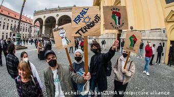 Demonstrators at a May 11, 2021 protest hold signs that say both: Israel Terrorist and Free Palestine.