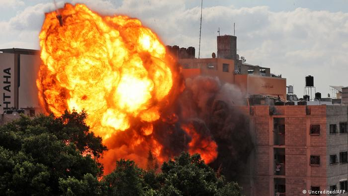A picture taken on May 13, 2021 shows a ball of fire engulfing the Al-Walid building which was destroyed in an Israeli airstrike on Gaza city early in the morning