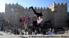A Palestinian youth performs a back flip at the Damascus Gate to the Old City of Jerusalem as people gather for Eid al-Fitr, marking the end of the Muslim holy month of Ramadan. Thursday, May 13, 2021. (AP Photo/Mahmoud Illean)