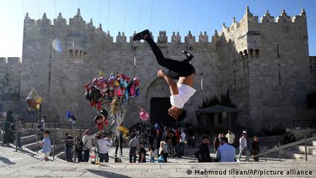 A Palestinian youth performs a back flip at the Damascus Gate to the Old City of Jerusalem as people gather for Eid al-Fitr