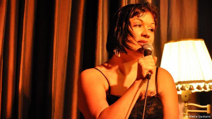 Aletia Upstairs singt auf einer Bühne vor einem roten Vorhang.