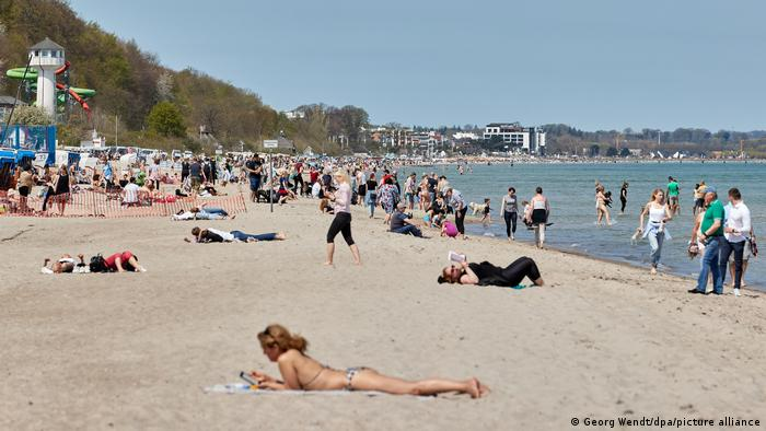 People on a beach in the test model region in the bay of Lübeck, Germany