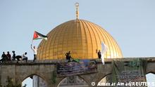 Men wave flags in front of the Dome of the Rock on the Temple Mount in Jerusalem