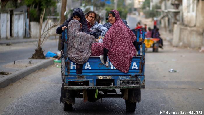 Palestinians riding on an auto rickshaw flee their homes