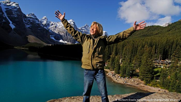 A woman stands on a rock above Moraine Lake in Banff, Canada