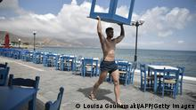 """*** Dieses Bild ist fertig zugeschnitten als Social Media Snack (für Facebook, Twitter, Instagram) im Tableau zu finden: Fach """"Images"""" *** 13.05.21 *** An employee carries a table in Kissamos, northwestern of the island of Crete, on May 13, 2021. - Greece easies the Covid-19 measures in welcoming international tourists on May 14. (Photo by Louisa GOULIAMAKI / AFP) (Photo by LOUISA GOULIAMAKI/AFP via Getty Images)"""