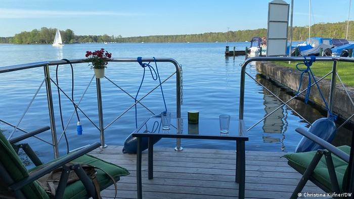 Houseboat rear deck with table and chairs looking out over a lake, Germany