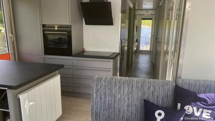 Interior of a luxury houseboat, with fully equipped kitchen and livng area