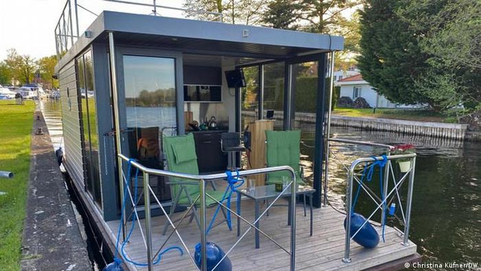 Germany, houseboat moored on a riverbank