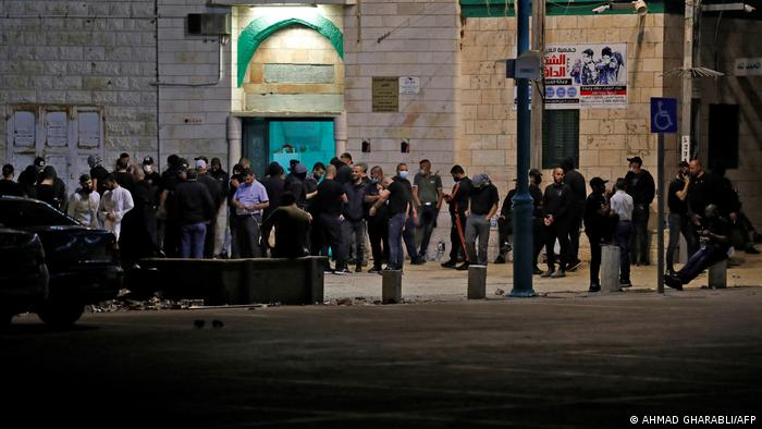 A large group of men stand in front of a mosque in the city of Lod, Israel