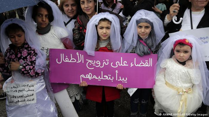Young Lebanese girls disguised as brides hold a placard as they participate in a march against marriage before the age of 18, in the capital Beirut.