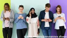 a group of diverse teenagers use mobile devices while posing for a studio photo in front of a pink background.    Modellfreigabe vorhanden