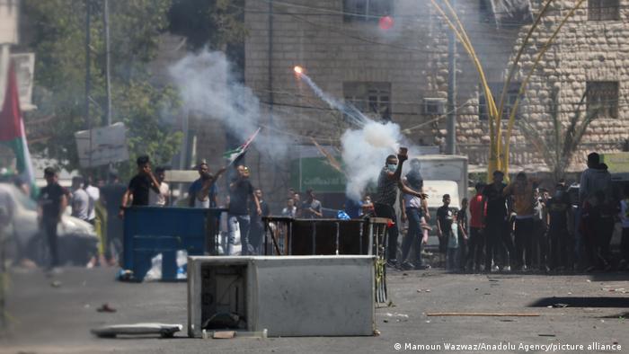 Manifestantes palestinos queman neumáticos y arrojan piedras durante una protesta contra los ataques de Israel, en Hebrón, Cisjordania (14.05.2021)