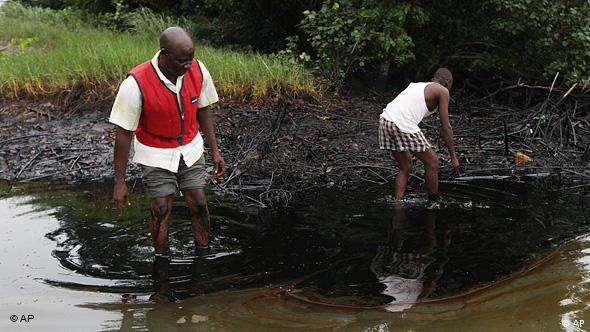 Men stand in a creek full of oil, oil all over their legs