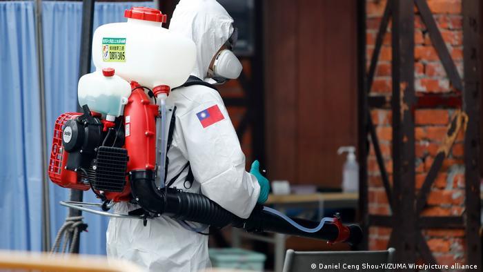 A man in a hazmat suit sprays chemicals