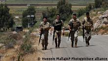 Lebanese army soldiers on a foot patrol at the Lebanese side of the Lebanese-Israeli border in the southern village of Kfar Kila, Lebanon, Saturday, May 15, 2021. On Israel's northern border with Lebanon, Israeli troops opened fire on Friday May 14 when a group of Lebanese and Palestinian protesters on the other side cut through the border fence and briefly crossed. (AP Photo/Hussein Malla)