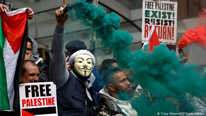 Pro-Palestinian activists and supporters let off smoke flares, wave flags and carry placards during a demonstration in London in support of Palestine