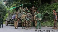 EDITORS NOTE: Graphic content / Armed government troops arrive outside the Gote Twin police station in Shan State on August 15, 2019, after it was attacked by ethnic rebel groups. - At least 14 have been killed in ongoing fighting on August 15 between Myanmar's military and rebels who mounted a series of attacks, including an unprecedented strike on an army academy, apparently in retaliation for massive drug seizures. (Photo by STR / AFP) (Photo credit should read STR/AFP via Getty Images)