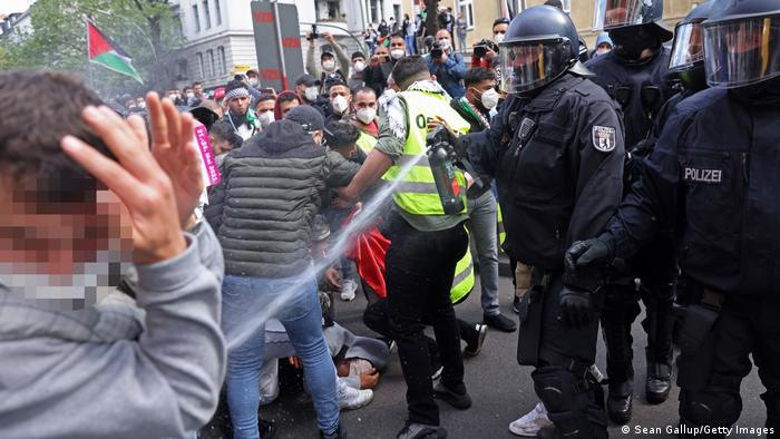 A riot police officer fires pepper spray at protesters