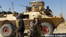 Four Afghan military personnel in and around an armored vehicle at Laschkar Gah