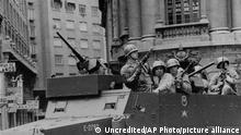 FILE - In this Sept. 12, 1973 file photo, soldiers try to spot snipers shooting from the upper floors of a government building in Santiago, Chile, during a coup against President Salvador Allende's government. Chile marks the 45th anniversary of the coup led by Pinochet overthrowing Allende, on Wednesday, Sept. 11, 2018. (AP Photo, File)