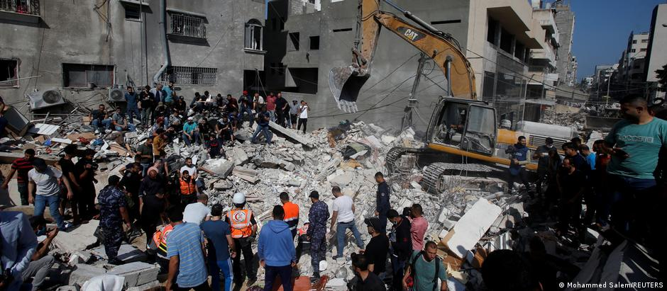 Rescuers and onlookers stand at the site of a demolished building in Gaza as a bulldozer moves rubble