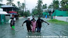 Officials rescue a local resident from a flooded area of Kochi, India