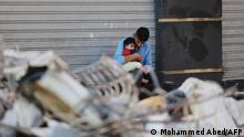 A Palestinian man holds his son as he sits outside a closed shop in front of his destroyed home in a residential neighbourhood in Gaza City early on May 16, 2021, following massive Israeli bombardment of the Hamas-controlled enclave. - The previous day, an Israeli air strike flattened a 13-floor building housing Qatar-based Al Jazeera television and the US news agency the Associated Press in the Gaza Strip. (Photo by MOHAMMED ABED / AFP)