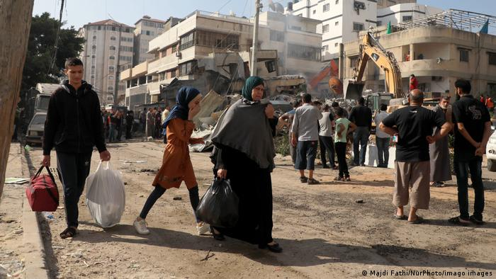 People move about Gaza with bags of belongings as a crows watches tractors clear rubble