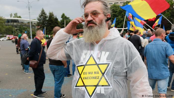 Un protestatar cu steaua galbenă pe care o purtau evreii în Germania nazistă