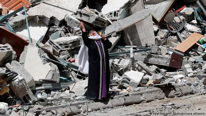 Жінка на руїнах будинку, зруйнованого у Секторі Гази