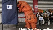 Große Dinausaurierfigur vor Wahlkabine - im Hintergrund sitzt der Wahlvorstand