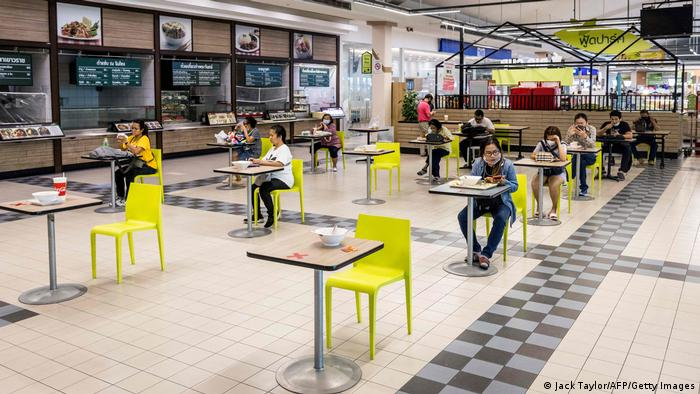 Customers eat their meals at socially distanced tables in a mall in Bangkok on May 17, 2021