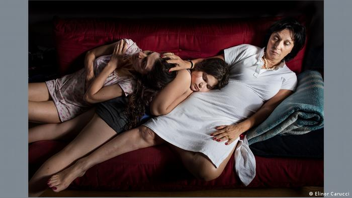 A picture by Elinor Carucci, 'Three Generation': three generations of women lying on a sofa.