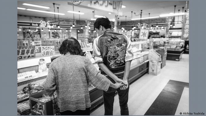 Akihito Yoshida's black-and-white photograph, an older woman holding a taller man's hand in a supermarket.