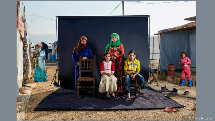 A photograph by Dario Mitidieri: A family portrait in front of a black photo backdrop set up in a refugee camp, with one empty chair.