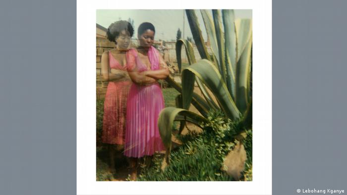 Lebohang Kganye's photograph. two women in a similar pose, wearing a pink dress, standing next to a large plant.
