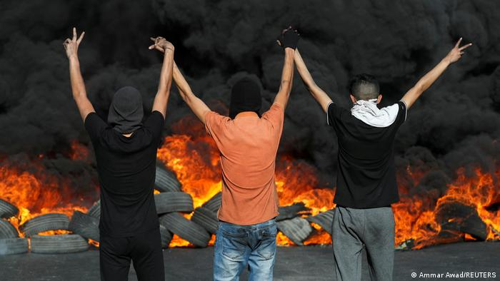 Three men seen from the back raising their arms before a pile of burning tires