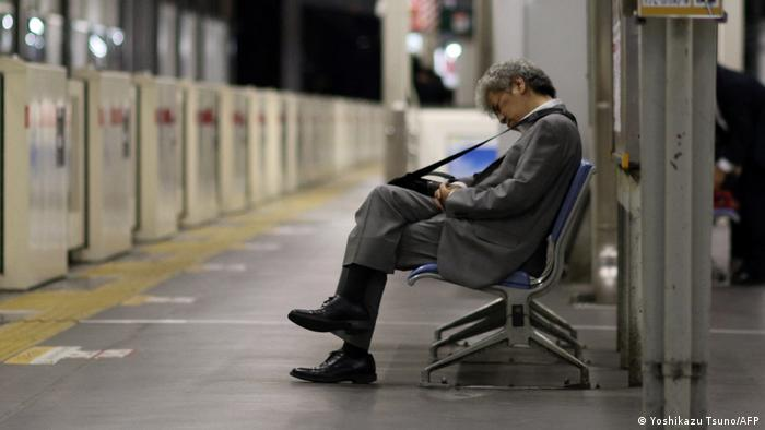 This picture taken on May 22, 2015 shows a businessman sleeping on a bench at a Tokyo train station
