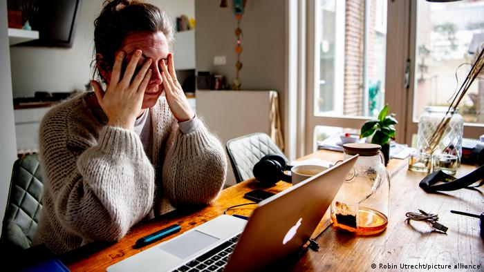 Woman sitting in front of her laptop at her dining room table at home, with her hands to her face