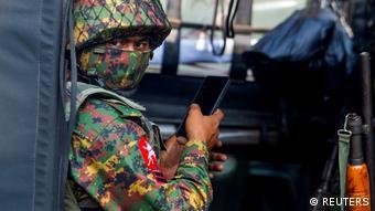 Солдат армии Мьянмы с мобильным телефоном
