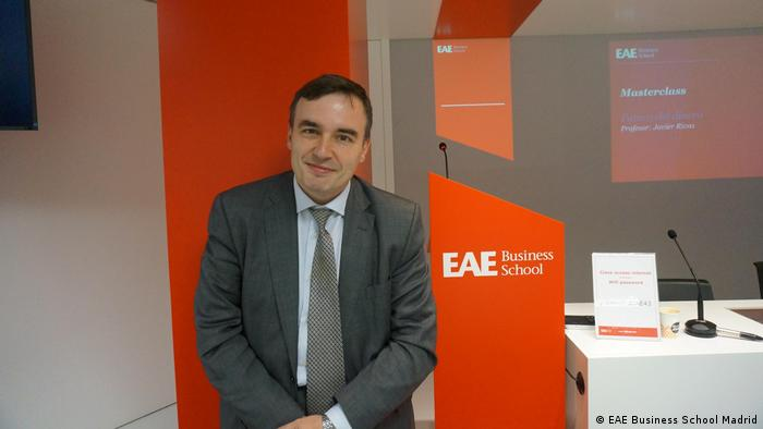 A picture of Javier Rivas with him standing next to a billboard reading EAE Business School