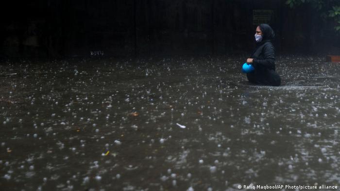Seorang perempuan berjalan di tengah banjir besar di Mumbai