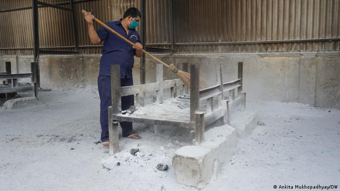 A man sweeps ash from a funeral pyre