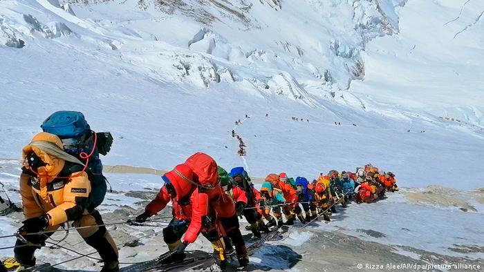 En una larga cola, los escaladores suben por un camino justo debajo del campamento cuatro. A pesar de la pandemia, ha habido un número récord de visitantes en el Monte Everest.