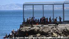 Spanish Guardia Civil officers try to stop people from Morocco entering into the Spanish territory at the border of Morocco and Spain, at the Spanish enclave of Ceuta
