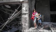 TOPSHOT - Palestinian children salvage toys from their home at the Al-Jawhara Tower in Gaza City, on May 17, 2021, which was heavily damaged in Israeli airstrikes. (Photo by ANAS BABA / AFP) (Photo by ANAS BABA/AFP via Getty Images)